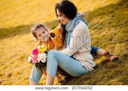 Daughter And Mother Sitting In Park
