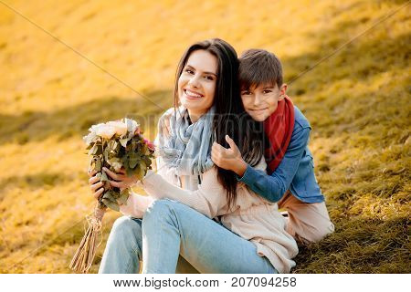 Happy woman sitting on a grassy lawn and holding bouquet of flowers while son hugging her