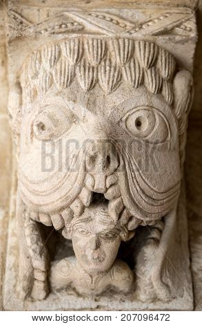 MONTMAJOUR FRANCE - JUNE 26 2017: Monster or Tarasque Devouring a Sinner c12th Romanesque Carving in the Cloisters Montmajour Abbey near Arles Provence France