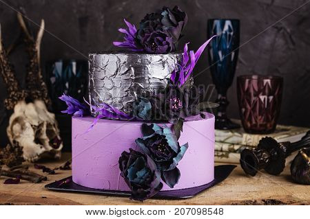 Tiered Cake With Black Flowers On Dark Background With Halloween Decorations