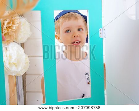 Boy playing in the studio. smiles and looks out through the decorative windows. in room