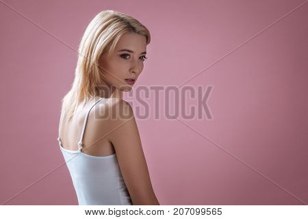 In frustration. Concentrated female person posing with back on camera and pressing teeth while posing on camera