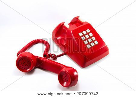 Red vintage telephone isolated on white background. Red telephone on call waiting.