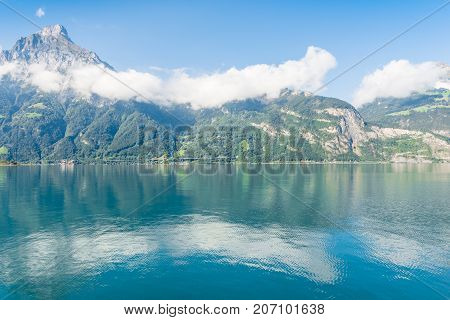 Stratocumulus clouds in the Alps mountains. Reflected in the water of Lake Lucerne.