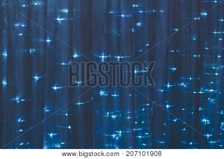 Christmas drape with lights of blue color - background is a Festive fabric.