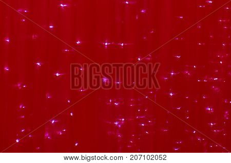 Christmas drape with lights of red color. The background is a Festive fabric.