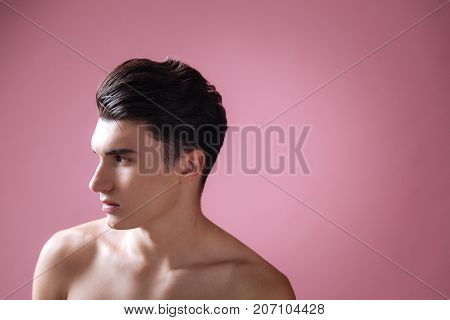 Have disdain. Serious male person pressing lips and wrinkling forehead while posing in studio
