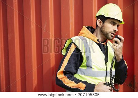 Docker guy in hard hat using walkie talkie side view
