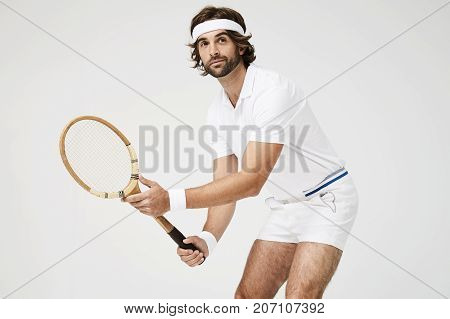 Tennis payer ready with racket in studio looking away
