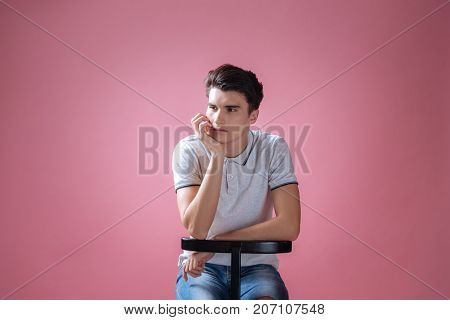 Must wait. Handsome male person wrinkling his forehead and leaning elbows on the chair while looking aside