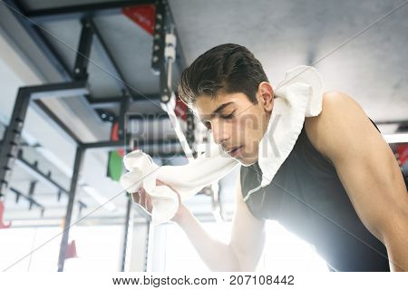 Young fit hispanic man in black sleeveless shirt in modern gym towel around his neck, wiping sweat off face