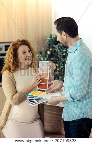 Your turn. Optimistic pleasant wife showing the card with the color to her husband while expressing interest and concern