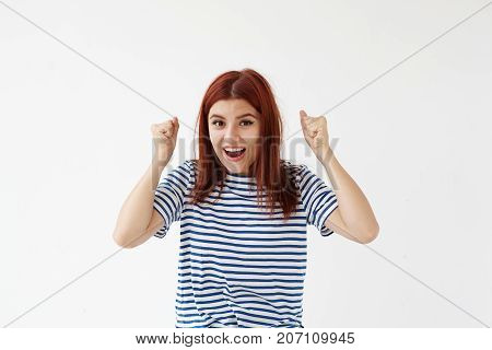 Euphoric young European lady in casual sailor shirt celebrating success exclaiming in excitement raising clenched fists in the air feeling exited and happy after she won in lottery. Body language