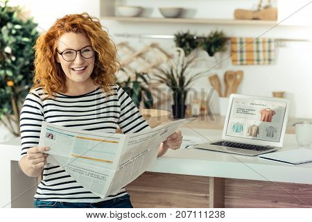 Latest news. Positive beautiful pregnant woman reading a newspaper while smiling and being interested
