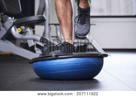 Dude jogging on bosu ball in gym close up
