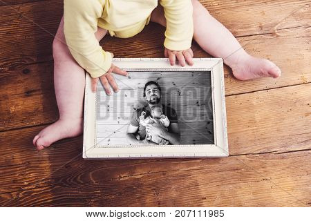 Unrecognizable little baby holding picture frame with photo of father and baby daughter. Studio shot on wooden background. Fathers day concept.