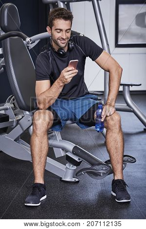 Athlete taking a break to ext on Smartphone smiling