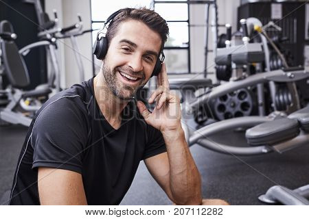 Gym bunny listening to tunes on headphones in gym