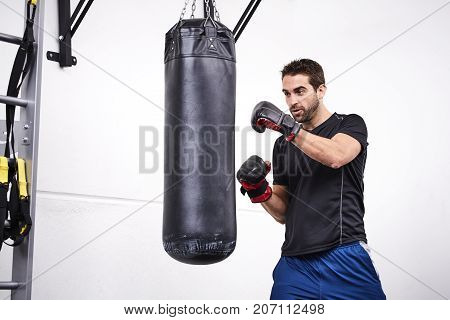 Boxing punch bag guy full of power in gym