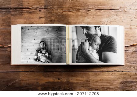 Photo album with pictures of young father and his cute newborn baby daughter. Fathers day concept. Studio shot on wooden background.