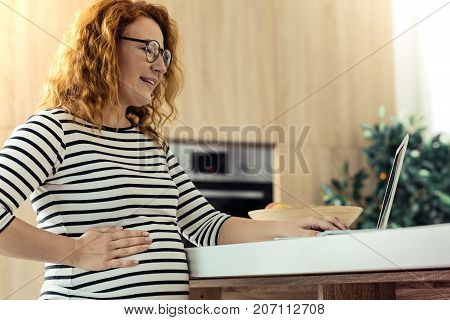 Slightly tired. Pretty smiling woman with glasses touching her belly while standing at the table and working with a laptop