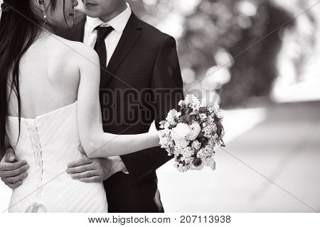 asian wedding couple hugging each other focus on the bouquet black and white.