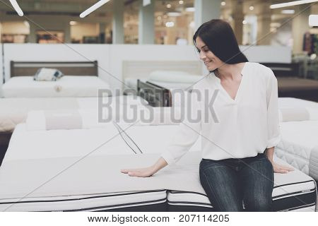 A Woman Chooses A Mattress In A Store. She Sits On It And Examines It.