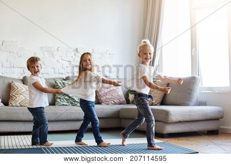 Candid shot of three cute children wearing similar white t-shirts and blue jeans walking barefooted on floor at home while dancing or doing conga line indoors on birthday party having happy faces