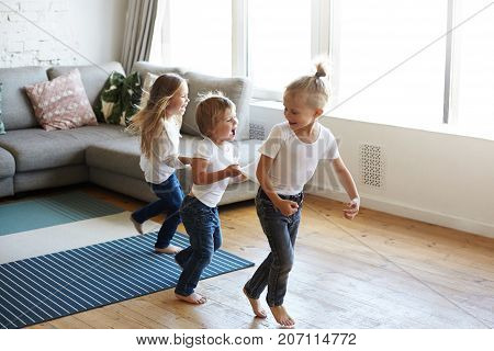Action freeze shot of three happy joyful children one girl and two boys pullin each other by clothes while doing conga line screaming in joy and excitement. Happiness childhood and leisure