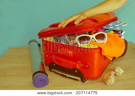Opened traveler case Suitcase on table. Woman putting clothes in suitcase closeup - Retro color