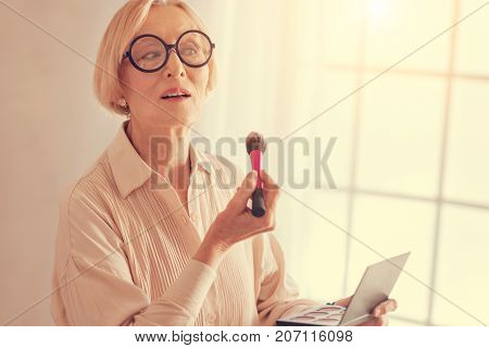 Preserve your beauty. Waist up of a nice beautiful aged woman holding a powder brush and applying dry concealer while doing her make up