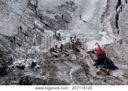 Walkers Secured With Ropes Preparing To Cross Alpine Glacier In Summer