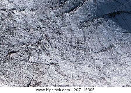 Walkers Secured With Ropes Crossing Alpine Glacier In Summer