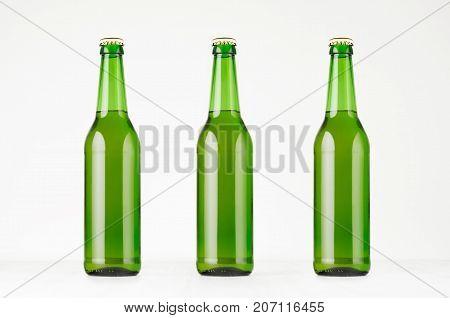 Three green longneck beer bottles 500ml mock up. Template for advertising design branding identity on white wood table.