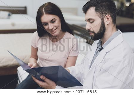 Consultant-orthopedist Helps The Girl To Choose A Mattress In The Store. He Holds A Blue Folder In H