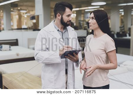 Consultant-orthopedist Helps The Girl To Choose A Mattress In The Store. He Interrogates A Woman