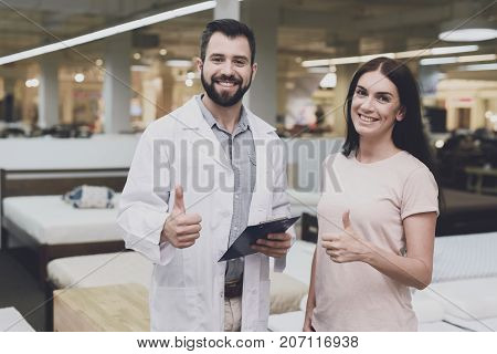 Thumbs Up. Consultant-orthopedist Helps The Girl To Choose A Mattress In The Store. He Interrogates