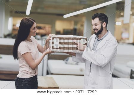 Consultant-orthopedist Helps The Girl To Choose A Mattress In The Store. He Offers Her A Mattress An