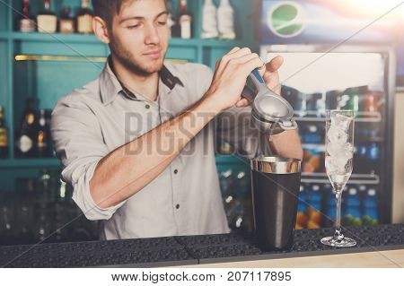 Professional bartender making cocktail with lime, squeezing it into mixing glass for citrus drink.