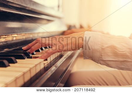 Hit the keys. Close up of hands of a female woman playing the piano and resting at home while enjoying the music