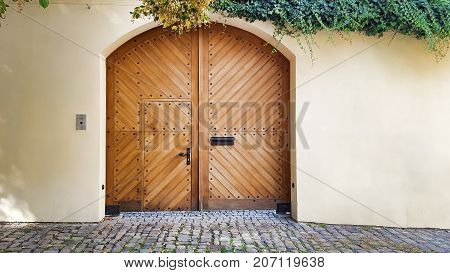 Wooden brown arch gate door white walls dangling ivy