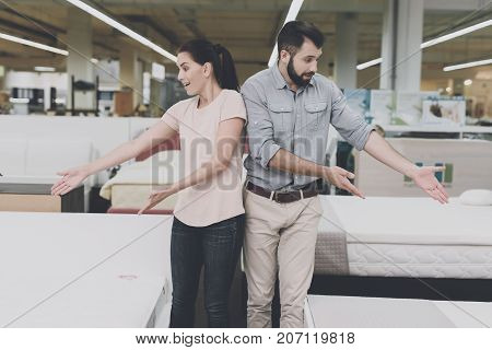 A Couple Chooses A Mattress In The Store. A Man Points To One, A Woman To Another