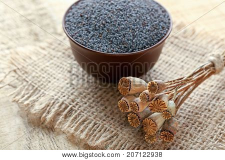 Poppy seeds and dried pods on sackcloth fabric