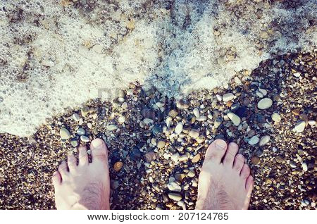 Bare feet of a man. It stands on a pebble beach next to the sea wave. Water foams. Stock toned photo.