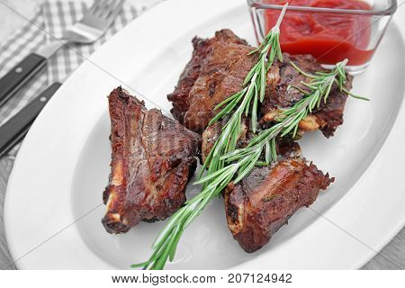 Plate with appetizing juicy spare ribs on table