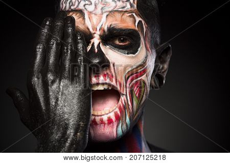 Halloween makeup concept, man covering zombie face with black painted hand. Detailed portrait of mans face with colores skeleton face.
