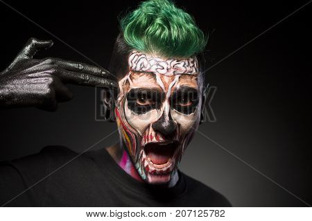 Halloween makeup, man with skeleton colored face touching temple. Face art. man with green hair and Halloween makeup isolated on black background.
