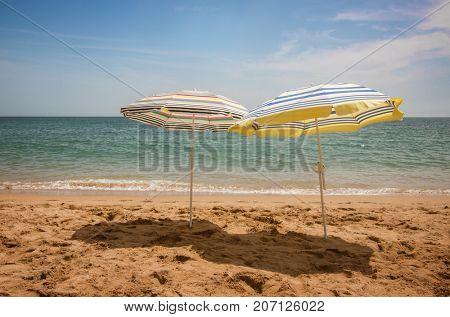 Two  beach sun shades alone in the sand of a beach