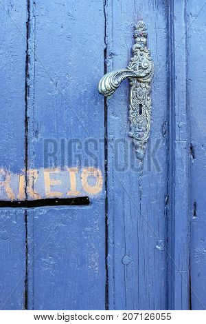 Detail of old and textured wooden blue door with metallic handle and postal mail slot