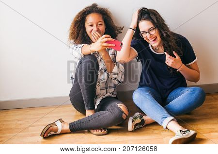Portrait of teenage girls having fun taking selfies in photo studio session